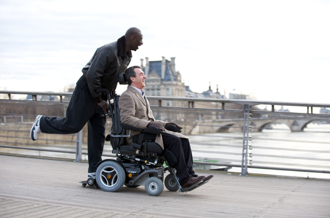 Driss (Omar Sy, left) and Philippe (François Cluzet, right) race down the streets of Paris.