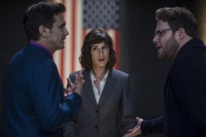 CIA Agent Lacey (Lizzy Caplan, center) briefs television star Dave Skylark (James Franco, left) and his producer Aaron Rapaport (Seth Rogen, right).
