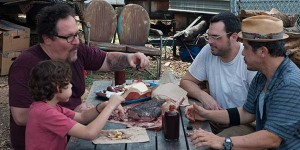 Carl Casper (Jon Favreau, back, to the left), his son Percy (Emjay Anthony, front, to the left), and their friend Martin (John Leguizamo, front, to the right) enjoy a good Texas BBQ.